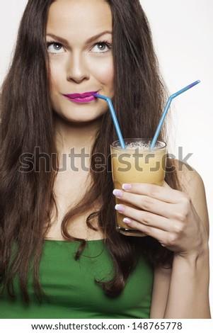 Go juicy. Young beautiful woman enjoying a healthy raw fruit vegetable juice. Studio shot. - stock photo