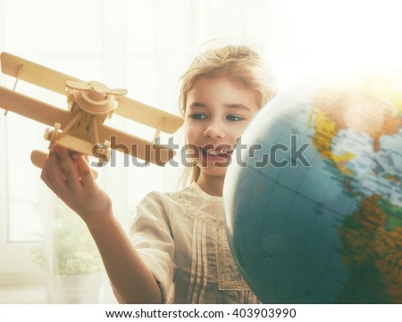 Go on an adventure! Cute child girl playing with toy airplane and globe.