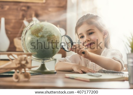 Go on an adventure! Happy cute child preparing for the journey. Pretty girl study the globe and choose a route of travel. - stock photo