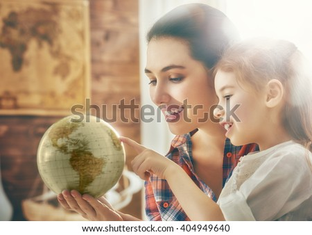 Go on an adventure! Happy family preparing for the journey. Mom and daughter study the globe and choose a route of travel. - stock photo