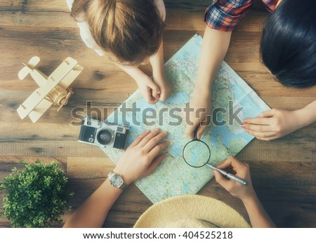 Go on an adventure! Happy family preparing for the journey. Mom, dad and daughter study the map and choose a route of travel. - stock photo