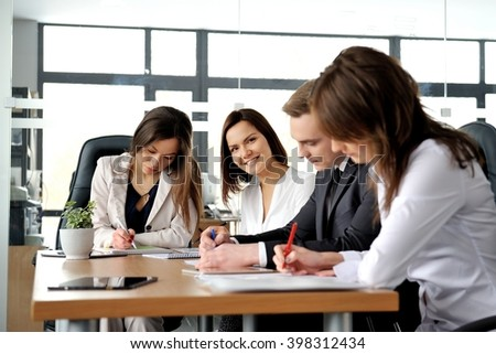 Go team! Group of young business people in a meeting at office. - stock photo