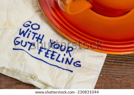 go with your gut feeling - advice or motivational reminder  on a napkin with cup of coffee - stock photo