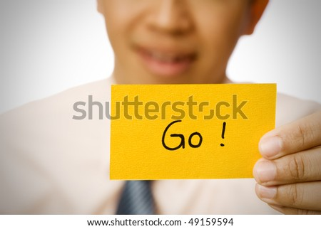 Go word on yellow card holding by businessman. - stock photo