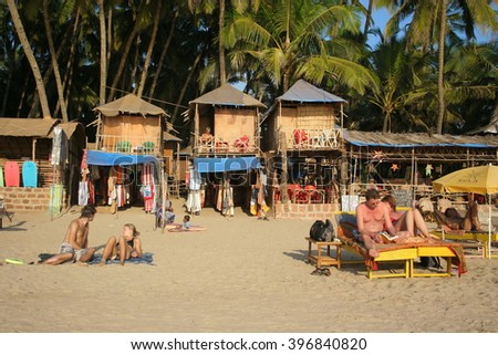 Goa, India - January 31, 2006: People relax on the Palolem beach near the bungalows