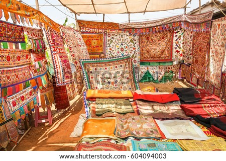 GOA, INDIA - MAR 1: Seller of antique carpets shows colorful embroidered bedspreads at the marketplace of oriental bazaar on March 1, 2017. Near 5 million tourists visit Goa. annually