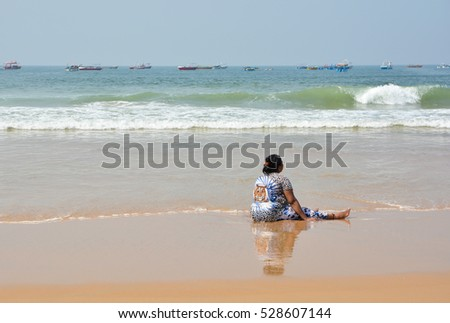 GOA,INDIA - NOVEMBER 10,2016: a Woman sits in the sea at Calangute beach.
