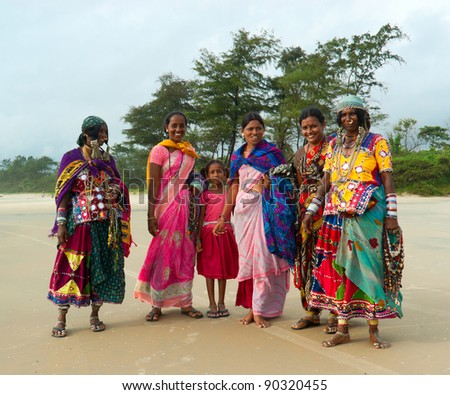 GOA, INDIA - SEPTEMBER 18: Unidentified Indian women and children in traditional dress pose for tourist photos on Goa beach, September 18, 2011 in Goa, India. This activity will provide a income stream for poor women on this Indian state - stock photo