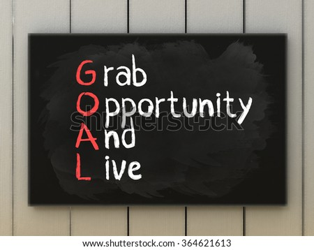 GOAL acronym on blackboard written with chalk. Grab opportunity and live. Motivation and business concept.