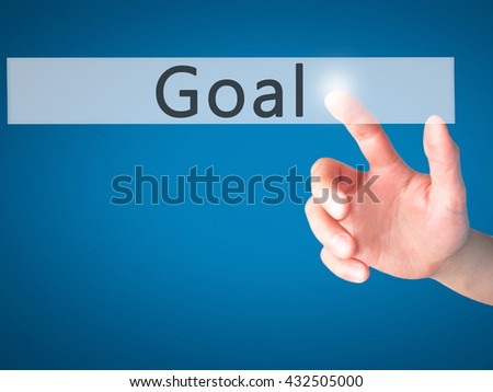 Goal - Hand pressing a button on blurred background concept . Business, technology, internet concept. Stock Photo