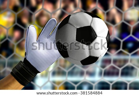 Goal keeper hand stopping a fast ball - stock photo