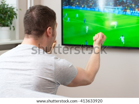 Goal! Man watching football match on television at home. - stock photo