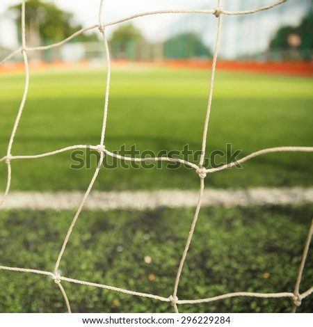 Goal net with green grass field - stock photo