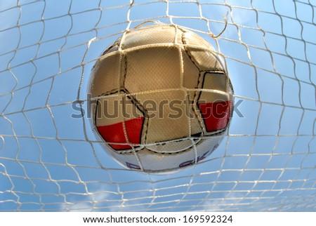 Goal, soccer ball in net - closeup - stock photo
