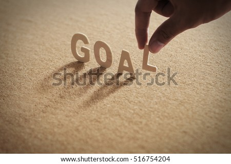 GOAL word of wood alphabet with shadow on cork board,compressed board