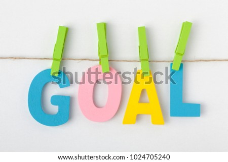 GOAL written in alphabet letters with wooden pinch on white background. Business Concept.