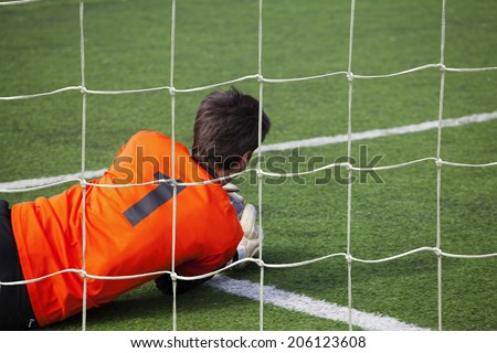 Goalkeeper catching a ball in the fall  - stock photo