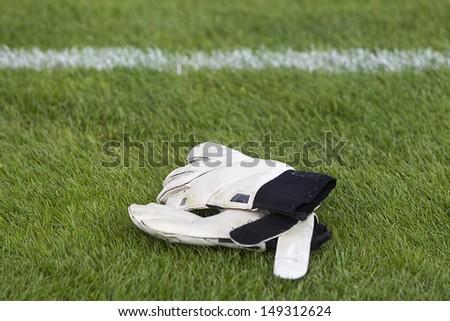 Goalkeeper gloves lying on football field - stock photo