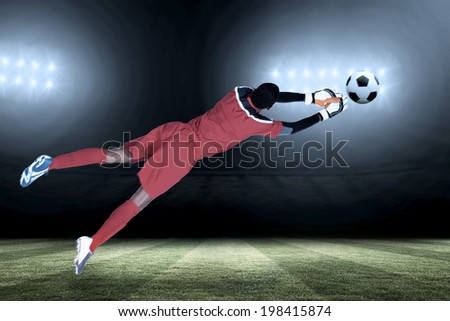 Goalkeeper in red making a save against football pitch under spotlights