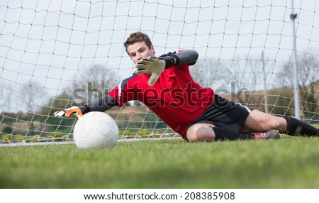 Goalkeeper in red saving a goal during a game on a clear day - stock photo