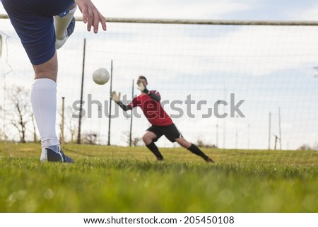 Goalkeeper in red saving a penalty on a clear day - stock photo