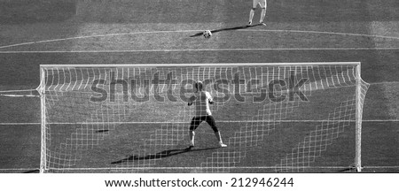 goalkeeper running and warming up before a football game. black and white photography   - stock photo