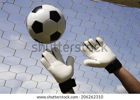 goalkeeper's hands reaching for the foot ball  - stock photo