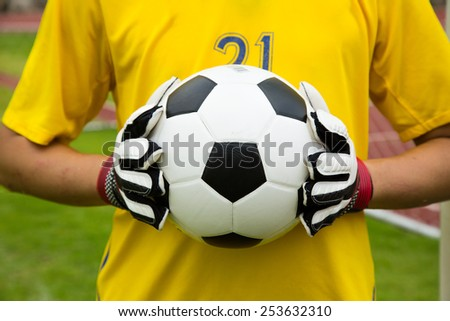 Goalkeeper used hands for catches the ball in match game - stock photo