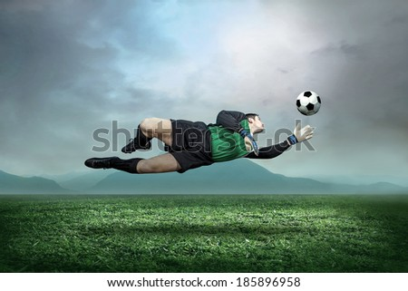 Goalkeeper with ball in action outdoors. - stock photo