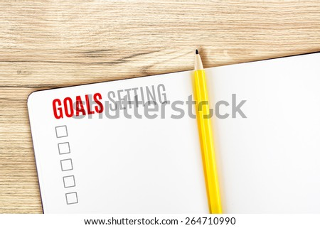 Goals Setting word on notebook lay on wood table,Template mock up for adding your goal. - stock photo