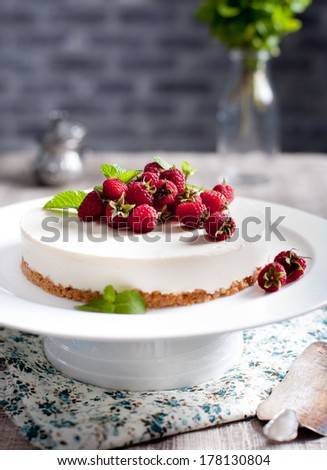Goat cheese cheesecake with fresh raspberries and mint leaves on top on a white plate - stock photo