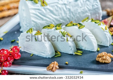 Goat cheese. Sliced the goat cheese on the table with pieces of pistachio. Cheese lying on a wooden table with raspberries and nuts - stock photo