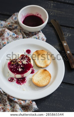 goat cheese with berry sauce, balsamic vinegar and nuts - delicious appetizers for wine on a dark wooden background - stock photo