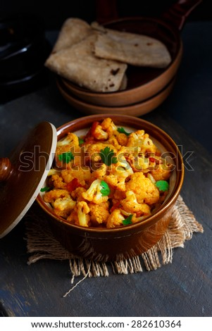 Gobi Sabji  Dry Cauliflower Curry served in a Brown Casserole along with some Roti's for lunch or dinner , Indian Food . - stock photo