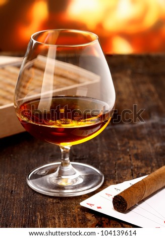 Goblet of cognac warming in front of the fire on a poker night with four aces and a cigar - stock photo