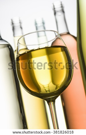 goblet with white wine and bottle on background