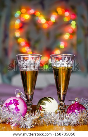 Goblets with sparkling wine and festive toys amid colorful heart-shaped Bokeh