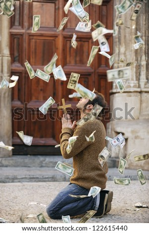 God is answering prayer: Man praying and money falling from the sky - stock photo