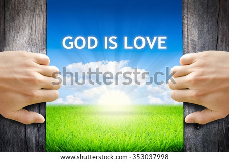 """God is Love. Hand opening an old wooden door and found wording """"God is Love"""" over green field and bright blue Sky Sunrise. - stock photo"""