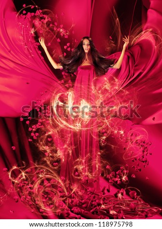 goddess of love in long red dress with magnificent hair makes a magic ritual of connecting hearts of people on red drapery, fabric - stock photo