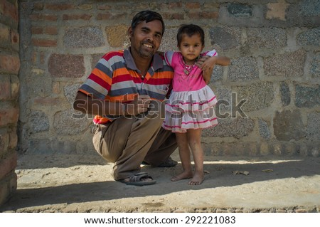 GODWAR REGION, INDIA - 15 FEBRUARY 2015: Happy father holds baby girl under shoulder in front of home. Child wears white and pink dress.