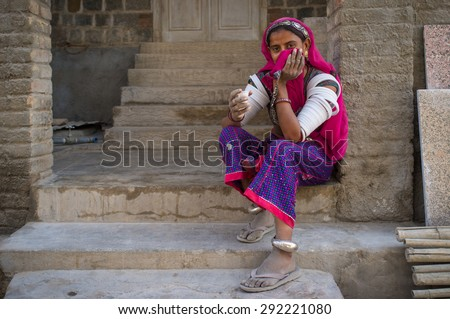 GODWAR REGION, INDIA - 15 FEBRUARY 2015: Indian tribeswoman covers face with headscarf and sits in front of home in saree decorated with upper-arm bracelets. - stock photo