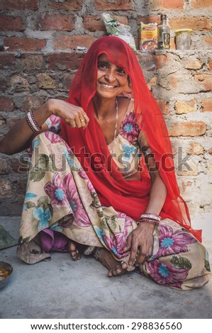 GODWAR REGION, INDIA - 13 FEBRUARY 2015: Indian woman in sari sits next to brick wall. Post-processed with grain, texture and colour effect. - stock photo