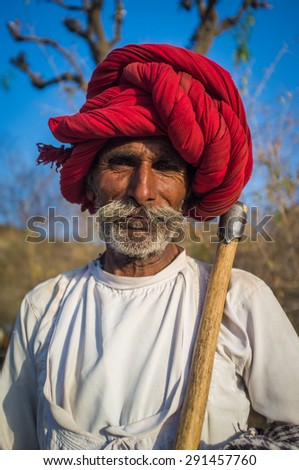 GODWAR REGION, INDIA - 13 FEBRUARY 2015: Rabari tribesman holds traditional axe and stands on field. Rabari or Rewari are an Indian community in the state of Gujarat. - stock photo