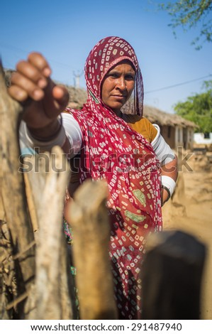 GODWAR REGION, INDIA - 13 FEBRUARY 2015: Rabari tribeswoman in sari decorated with traditional upper-arm bracelets holds gate of stable. Rabari or Rewari are an Indian community from Gujarat.