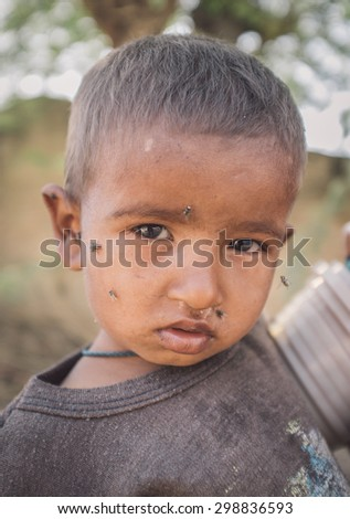 GODWAR REGION, INDIA - 15 FEBRUARY 2015: Young Indian child with flies around face. Post-processed with grain, texture and colour effect.