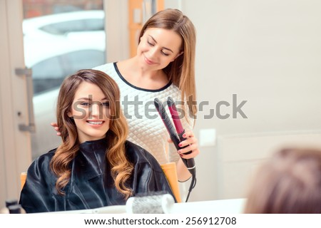 Going for big curls. Mirror reflection of a young beautiful woman discussing hairstyling with her hairdresser while sitting in the hair salon and getting her hair done with hair iron - stock photo