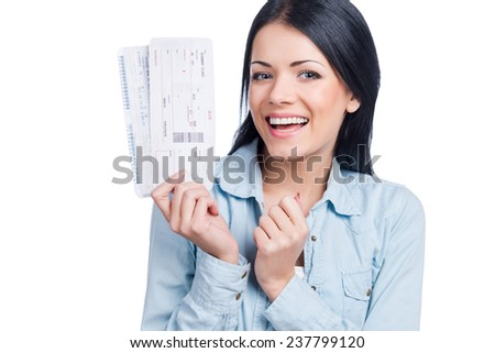Going on vacations. Beautiful young woman holding tickets and smiling while standing against white background - stock photo