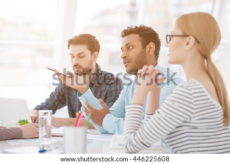 Going over the details. Young business partners offering his solution to problem at meeting in office - stock photo