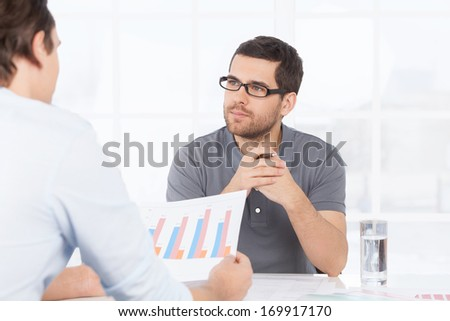Going over the numbers. Two confident business people in casual wear discussing something while one of them holding a paper with graph on it - stock photo